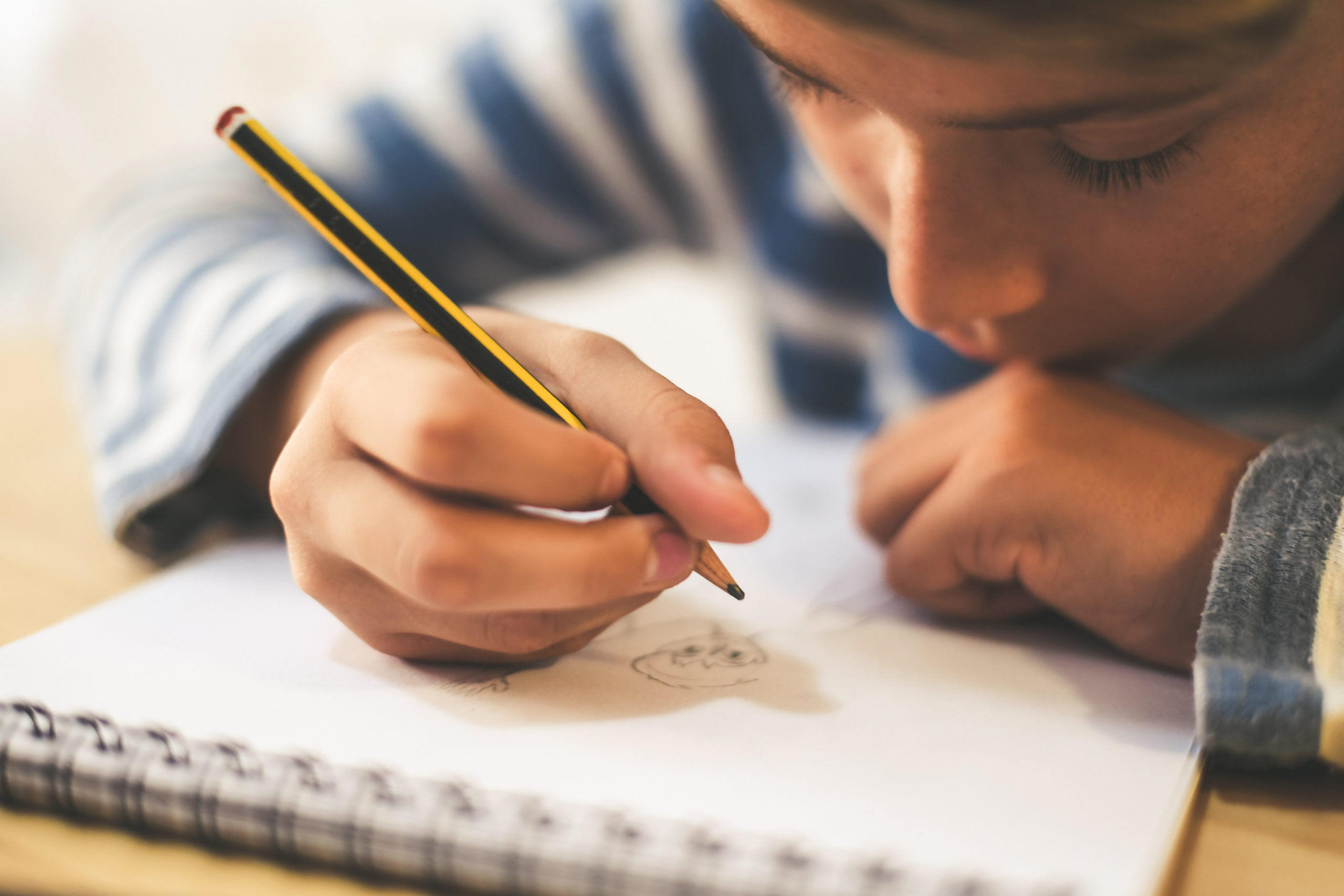 Child writing in notebook with a pencil